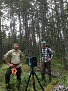 Two men stand in the woods with the scanner equipment between them.