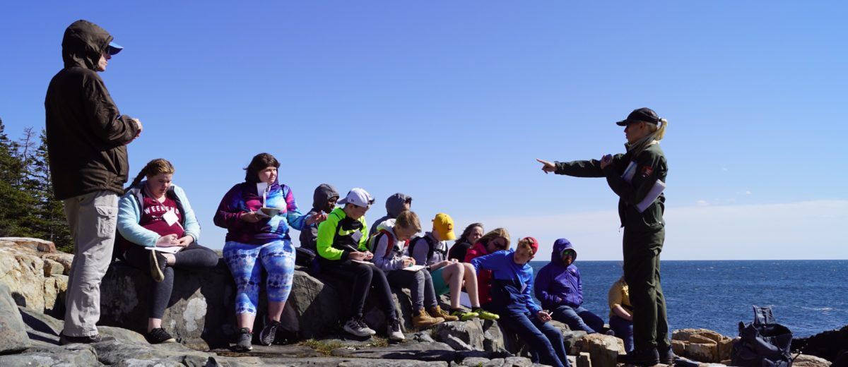 A National Park Student ranger instructs students on the rocks at Schoodic Point